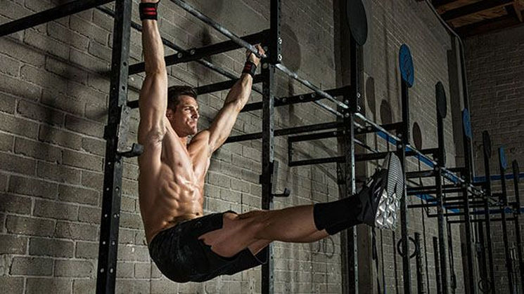 Young man performing abdominal crunches on bar in gym